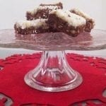 Coconut Christmas slice on a glass cake stand on a red felt snowflake shaped place mat